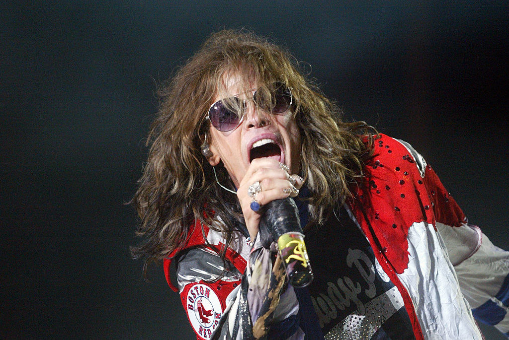 A photo of Steven Tyler performing on stage while wearing sunglasses in 2010.