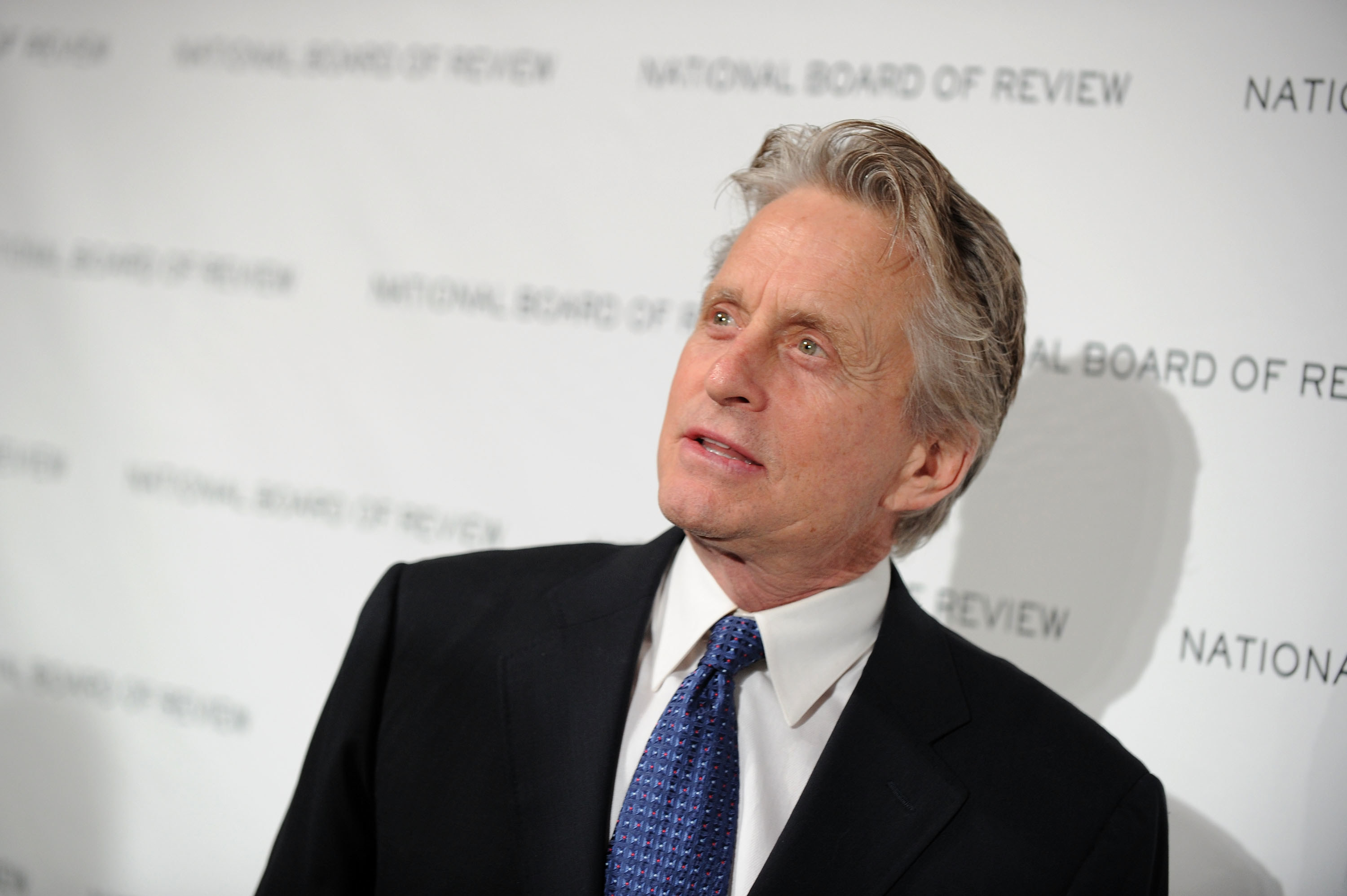 Michael Douglas attending the National Board of Review of Motion Pictures Awards gala in a black suit and blue tie in January 2010.
