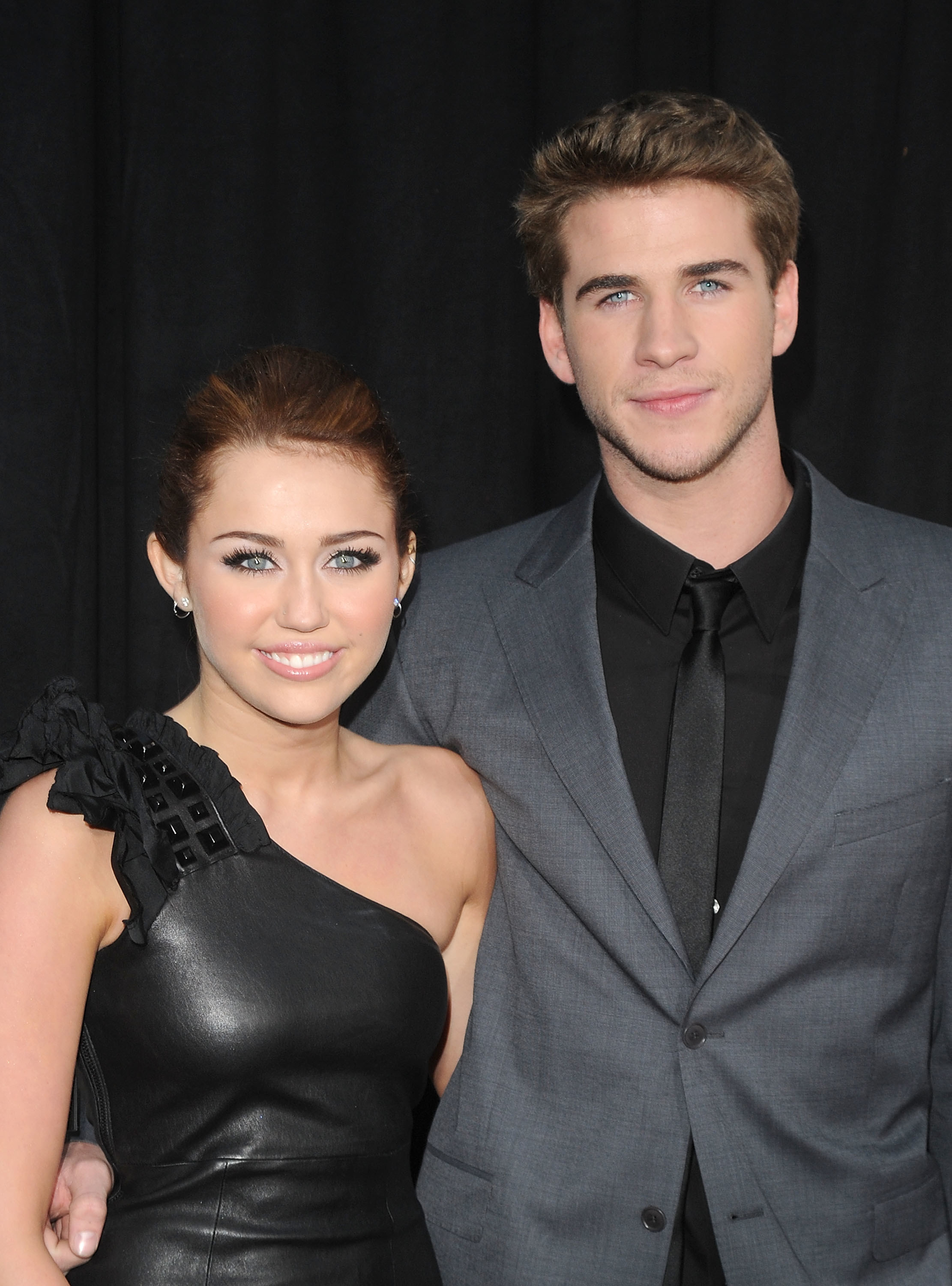 """Miley Cyrus in a black one shoulder pleather dress with Liam Hemsworth who is a grey suit with black shirt and black tie at the premiere of their movie """"The Last Song"""" in March 2010."""