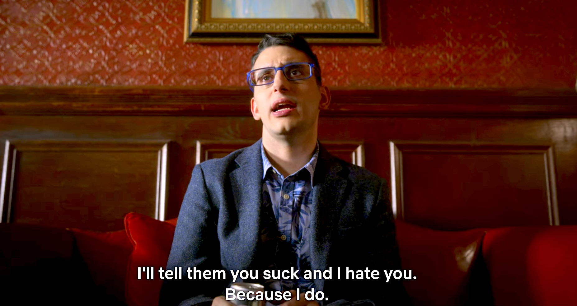 A still from The Politician showing Andrew sitting down in Payton's office against a red and mahogany wall in a blue suit saying I'll tell them you suck and I hate you because I do