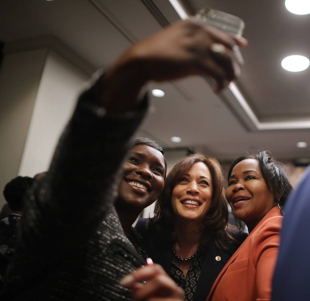 Three Black women look at a camera phone and smile
