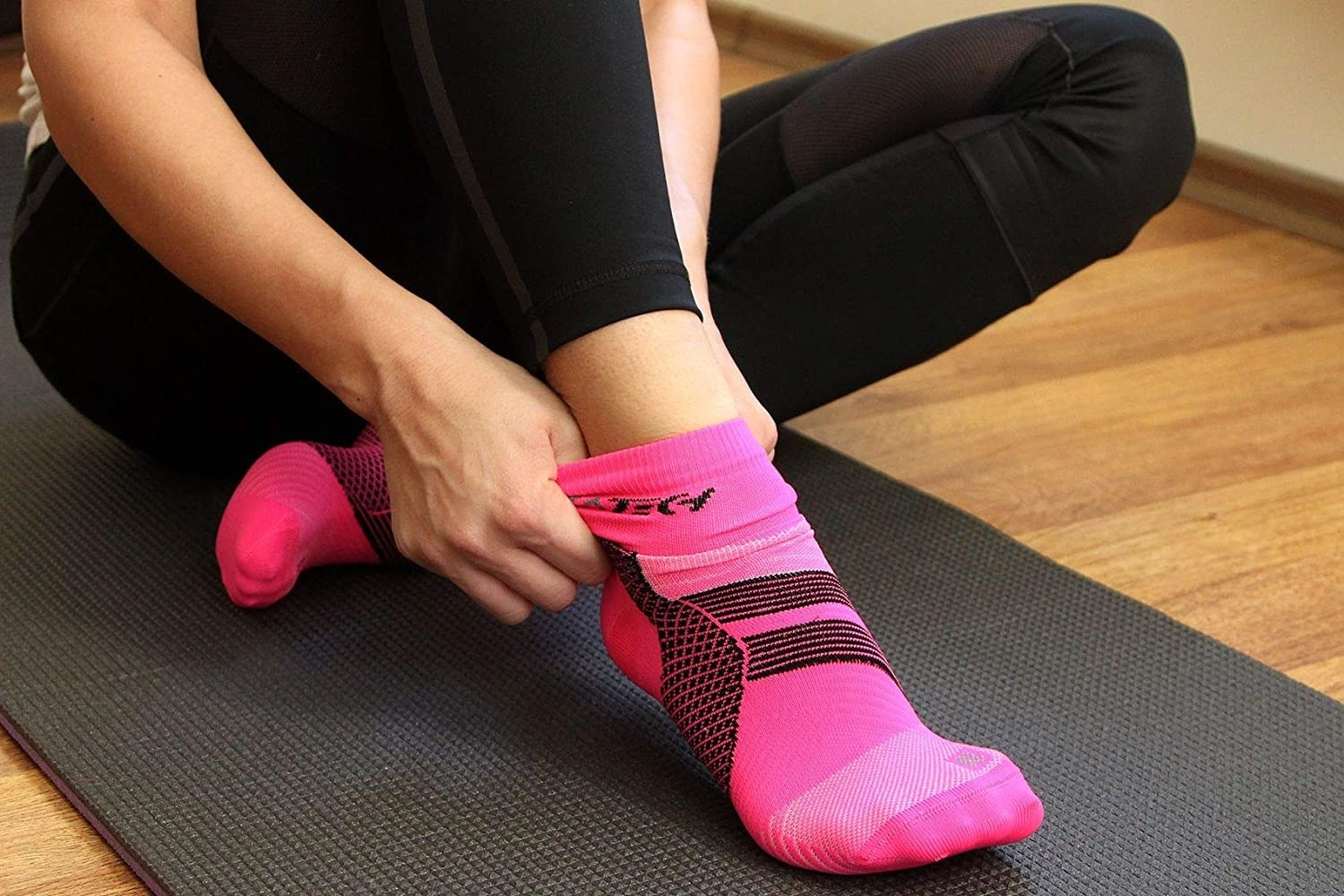 A person sitting on a yoga mat pulling on the compression socks