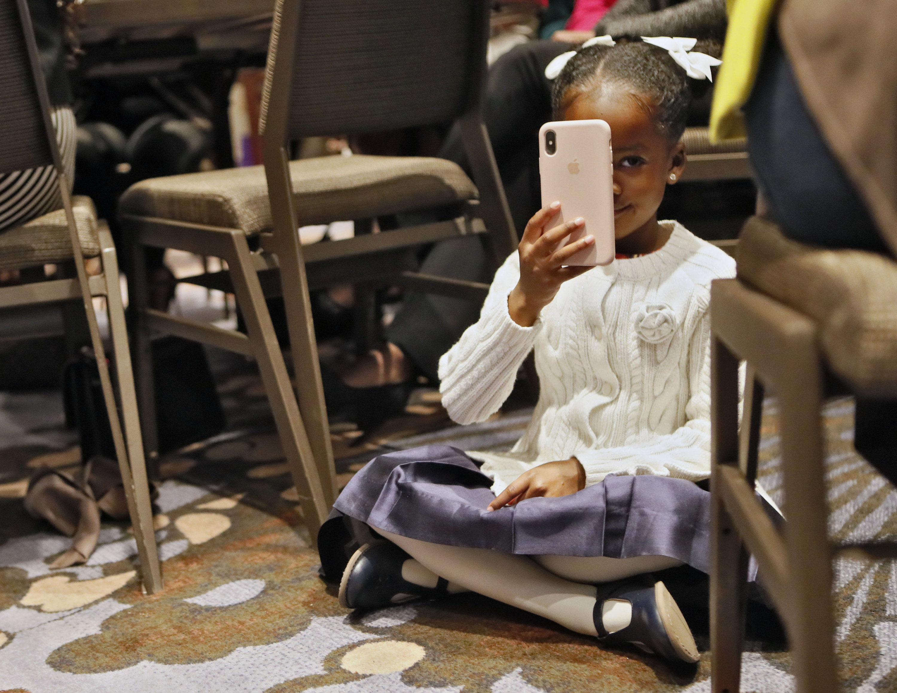 A young black girl sits on the floor and holds up a phone to take a picture