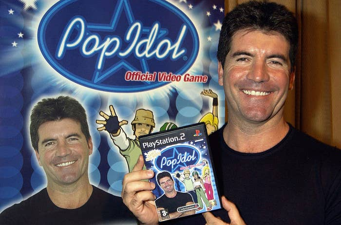 """Simon Cowell holding the """"Pop Idol"""" game with his own face plastered on it"""