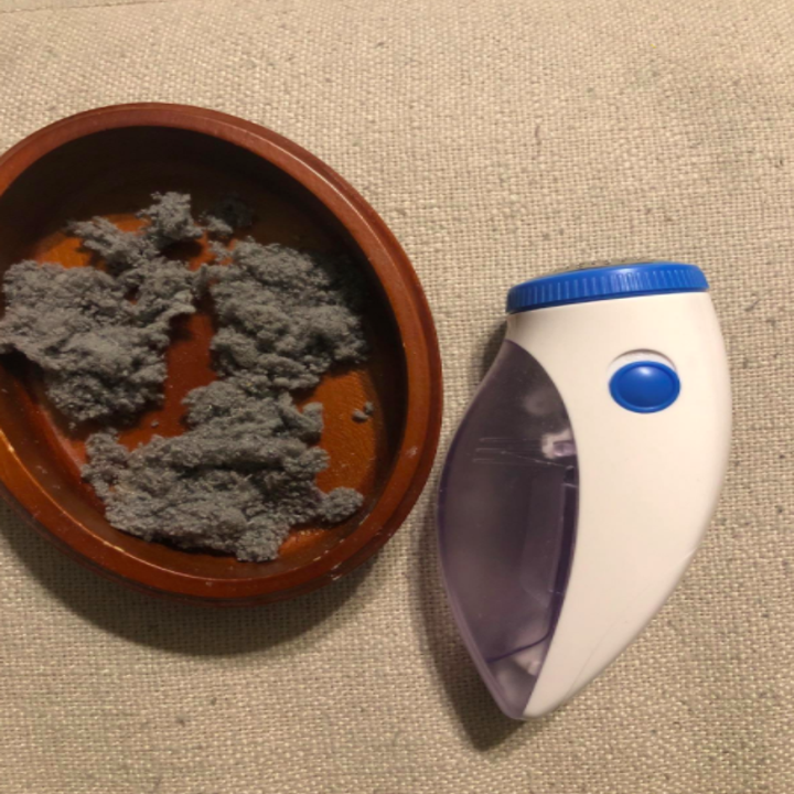 Reviewer photo showing the excess pilled fabric alongside the Fabric Shaver that the tool was able to effectively remove from their couch cushions