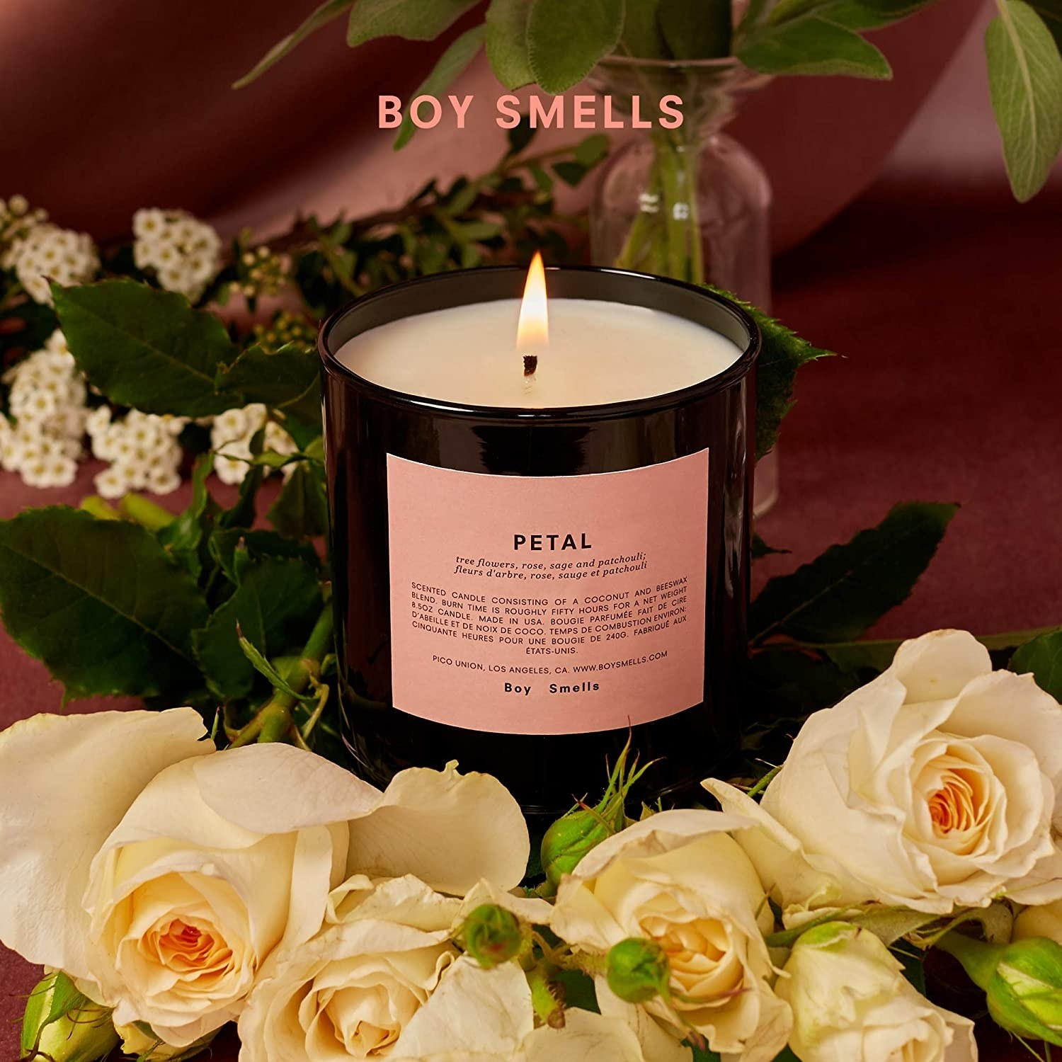 "boy smells' ""petal"" candle in a black jar with a pink label"