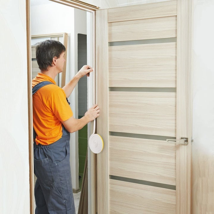 Product photo showing a person applying Weather Stripping to a door frame by simply sticking and rolling it along the edge of the frame, preventing drafts and increasing energy efficiency