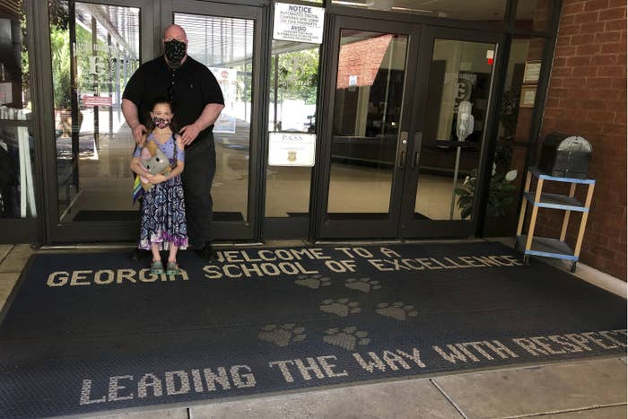 "A father wearing a mask stands behind his daughter who is also wearing a mask, on a rug that says ""Welcome to a Georgia School of Excellence. Leading the way with respect"""