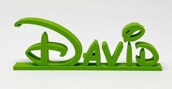 "The name ""David"" 3D printed in green Disney font on a flat base"
