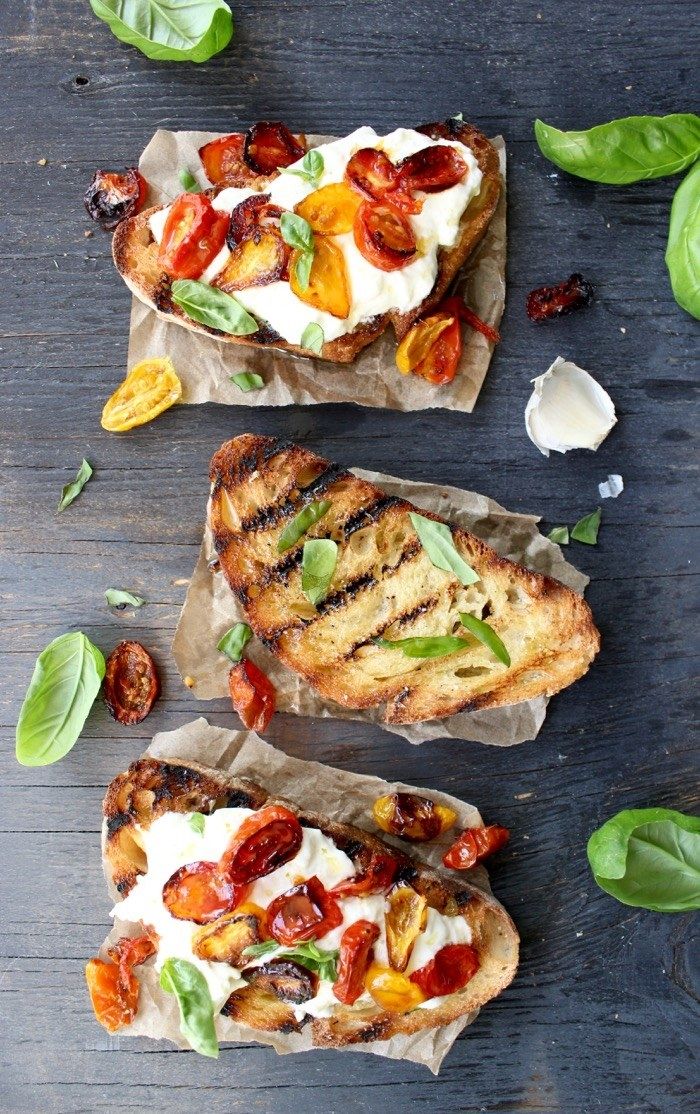 Three slices of charred ciabatta bread, two of which are topped with burrata cheese and roasted tomatoes.