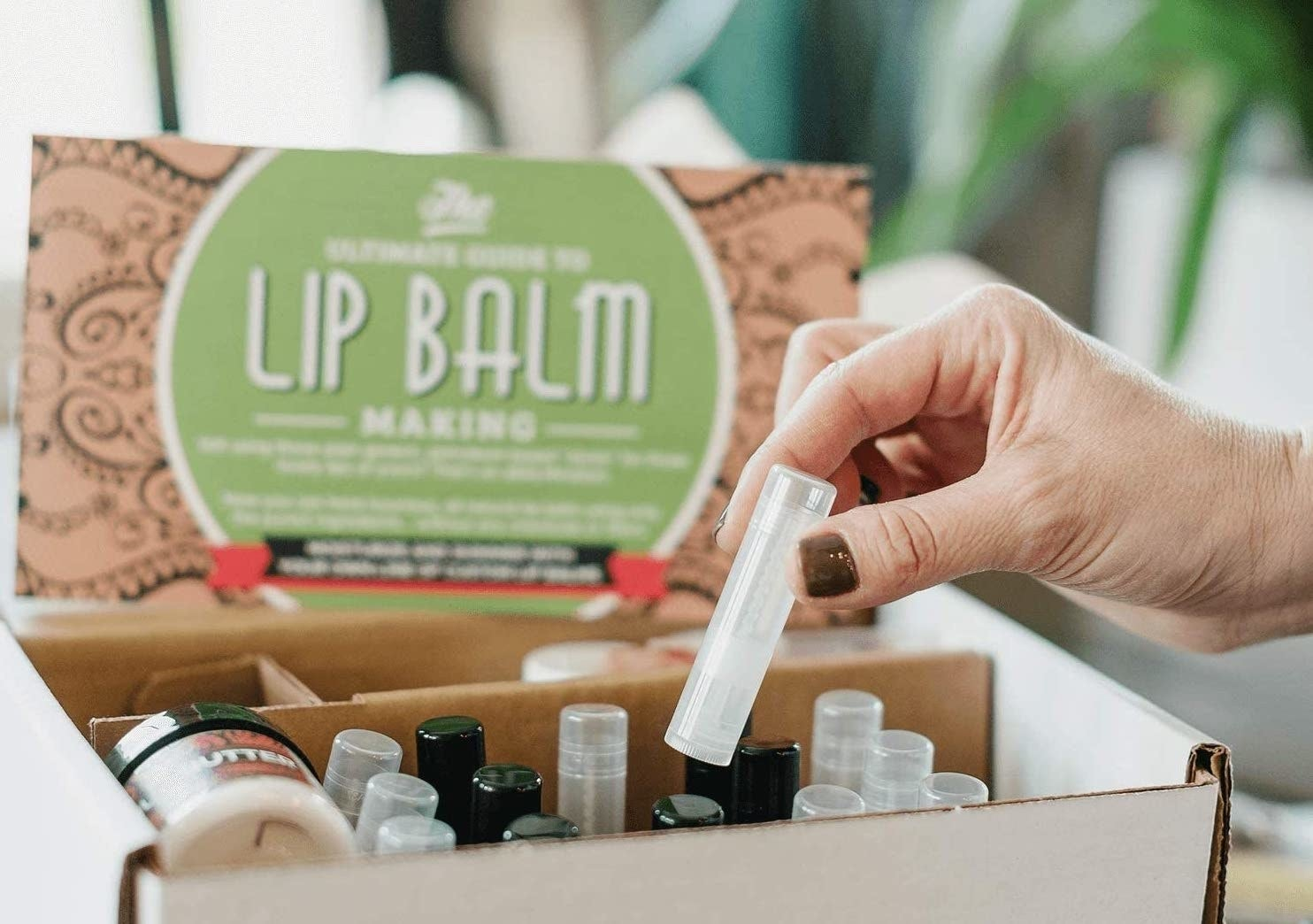 A hand removes a tube from the balm making kit