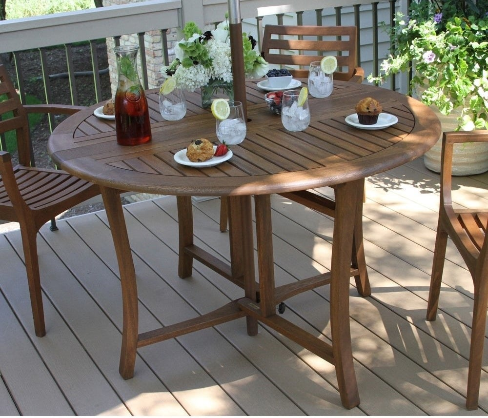 The circular teak-looking table with with snacks and glasses on top; it has space for an umbrella in the middle