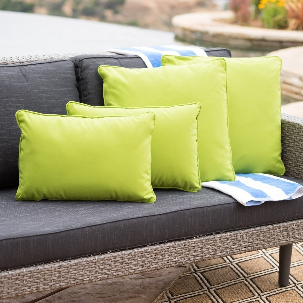 Four neon green pillows in two different sizes; two square, two rectangle