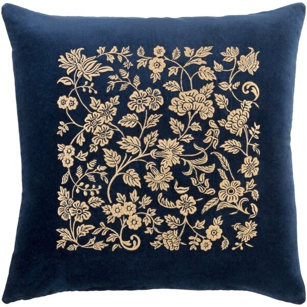 A square throw pillow in dark blue velvet with gold botanical filigree on the front