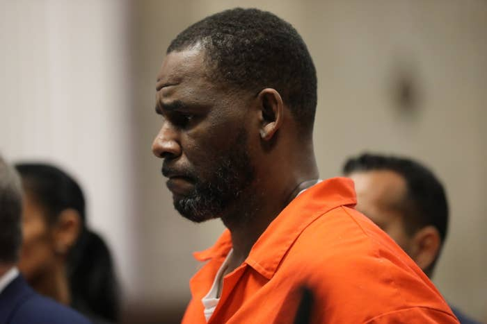 R. Kelly grimaces as he wears a prison uniform while in court