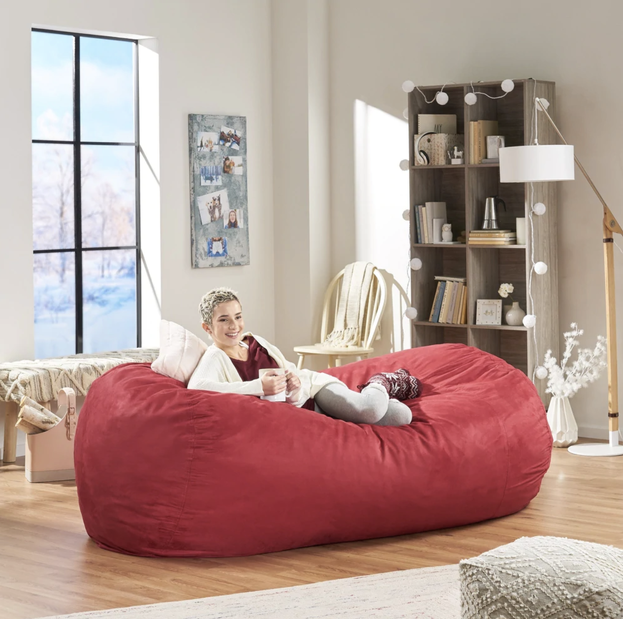 An adult laying down in the large bean bag chair