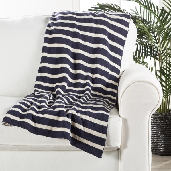 An ivory and navy striped throw blanket with a soft interior