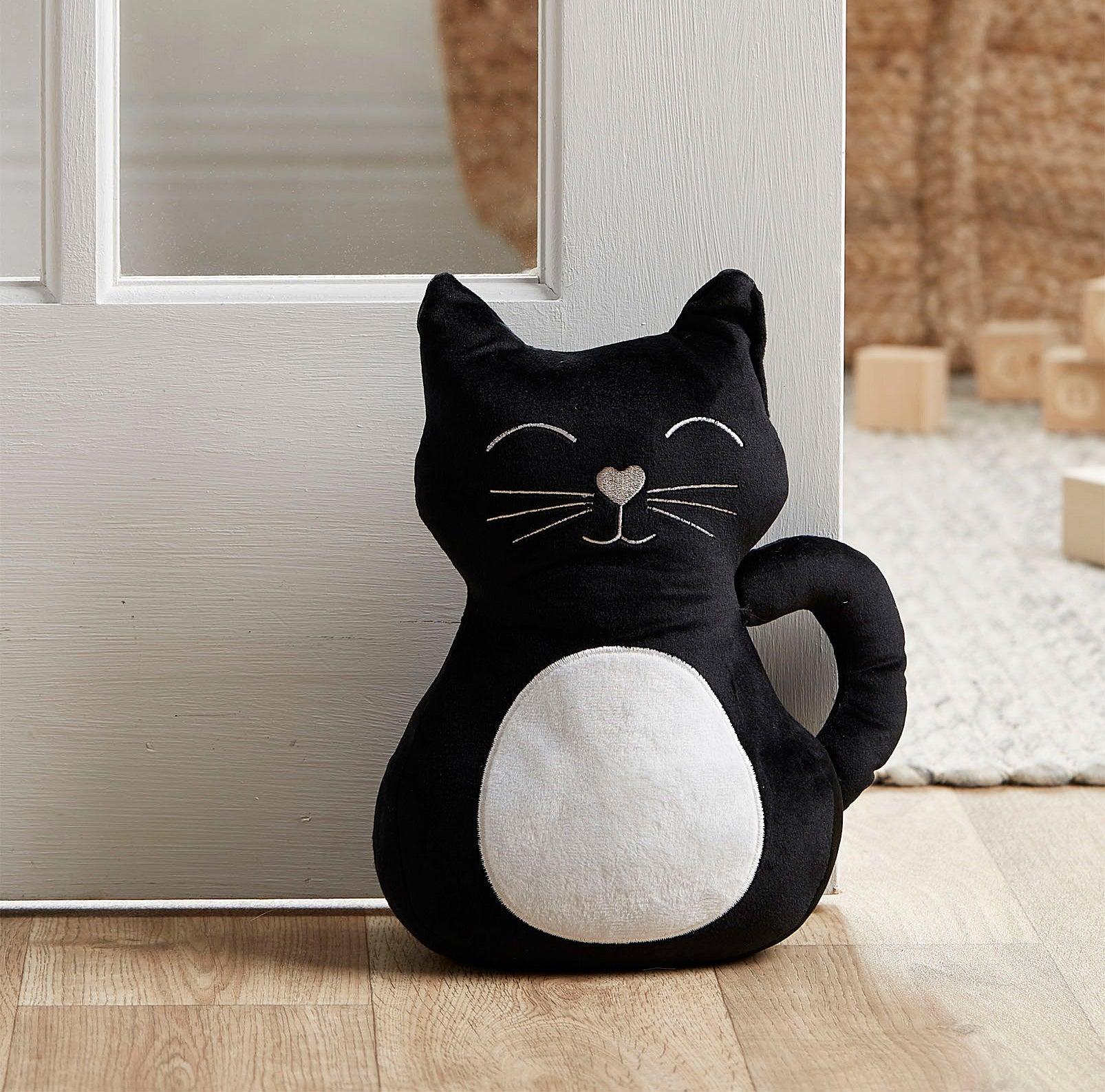 A smiling cat plush doorstopper