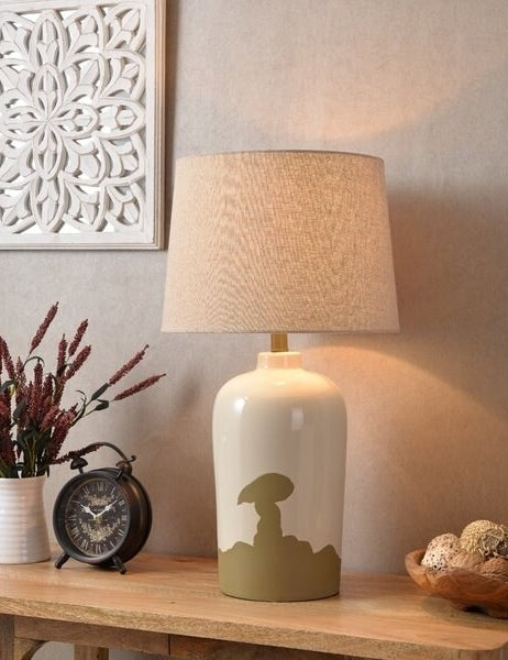 A porcelain table lamp with an ivory glaze on top and a textured olive worn and weathered pattern on the bottom that shifts up to the center of the lamp. The shade is a classic shape in ivory.