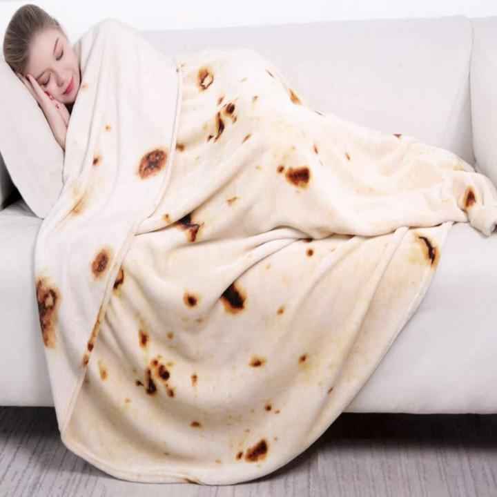 A model sleeping in a blanket that looks like a tortilla wrap
