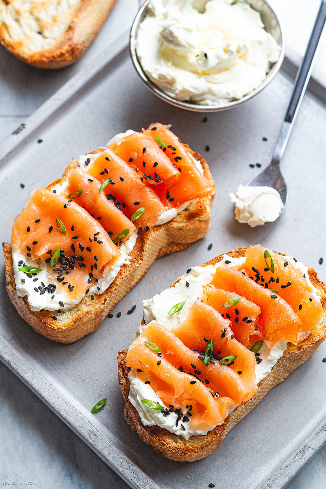 Two slices of thick toast topped with whipped cream cheese, smoked salmon, sesame seeds, and scallions.