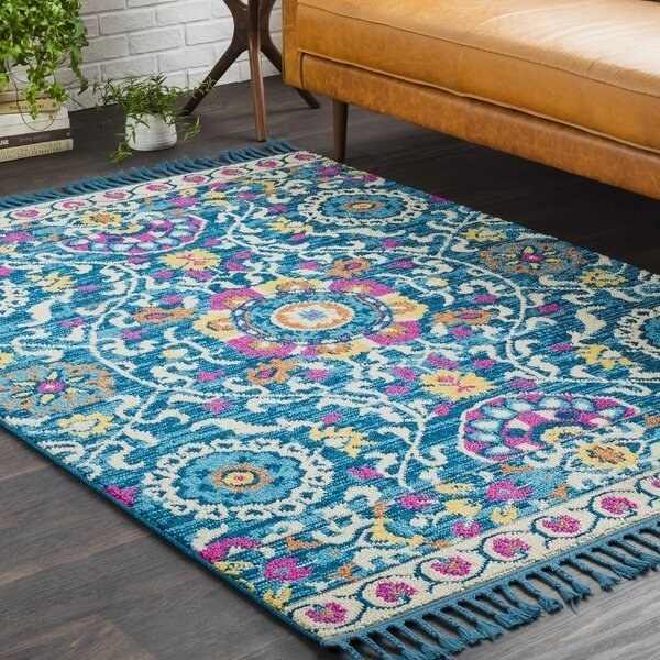 An area rug with a Turkish rug pattern in magenta, yellow, ivory, and blues with tassels on either end