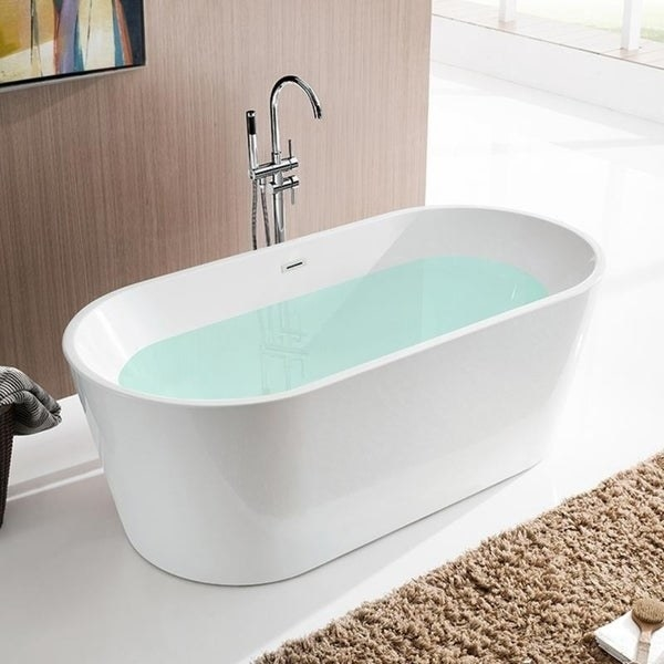 A white oval acrylic bathtub with water inside