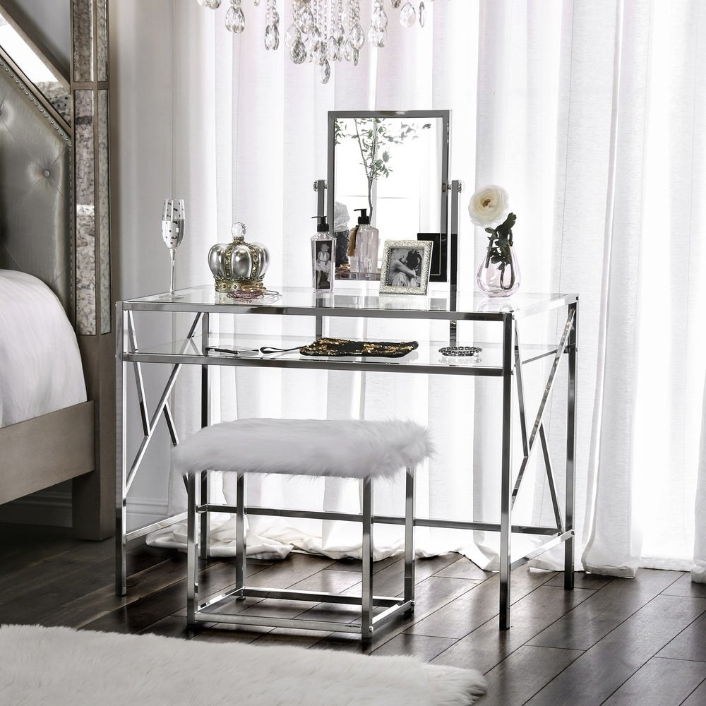 A vanity desk with a chrome base, a glass top, and a faux fur-seat on the chrome-based  stool