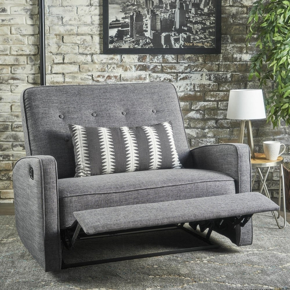 The gray armchair with a reclining foot rest and tufted back