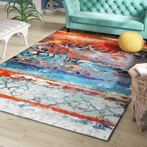 A multicolored rug with stripes, shapes, swirls, and other patterns that look painted and collaged on