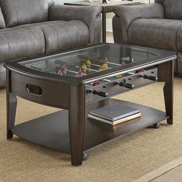 A brown coffee table with a glass top and a foosball game underneath it. The table has an open shelf at the bottom for storage.