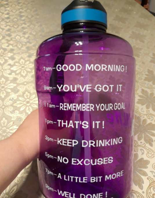 Reviewer photo of BuildLife motivational water bottle in purple, featuring time markers from 7am-9pm so you always know how much more water you have left to drink in the day and can easily pace yourself