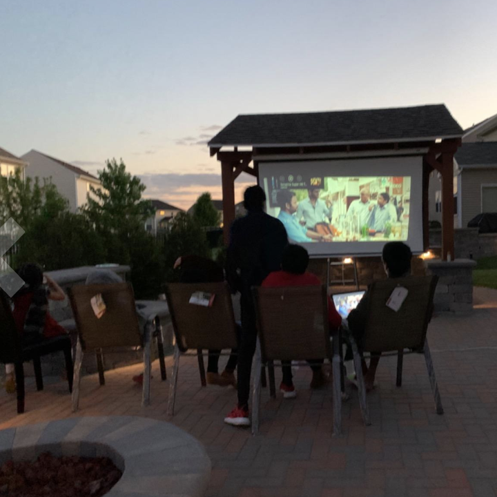 a reviewer using the movie projector outside