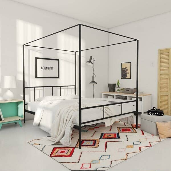 A black metal piping bed frame with a straight headboard and baseboard and connected canopy piping above