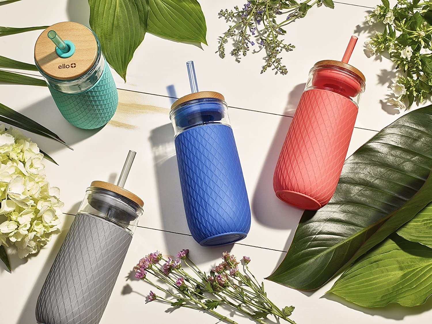 Product photo showing the Ello glass tumbler in gray, teal, blue and coral colors.