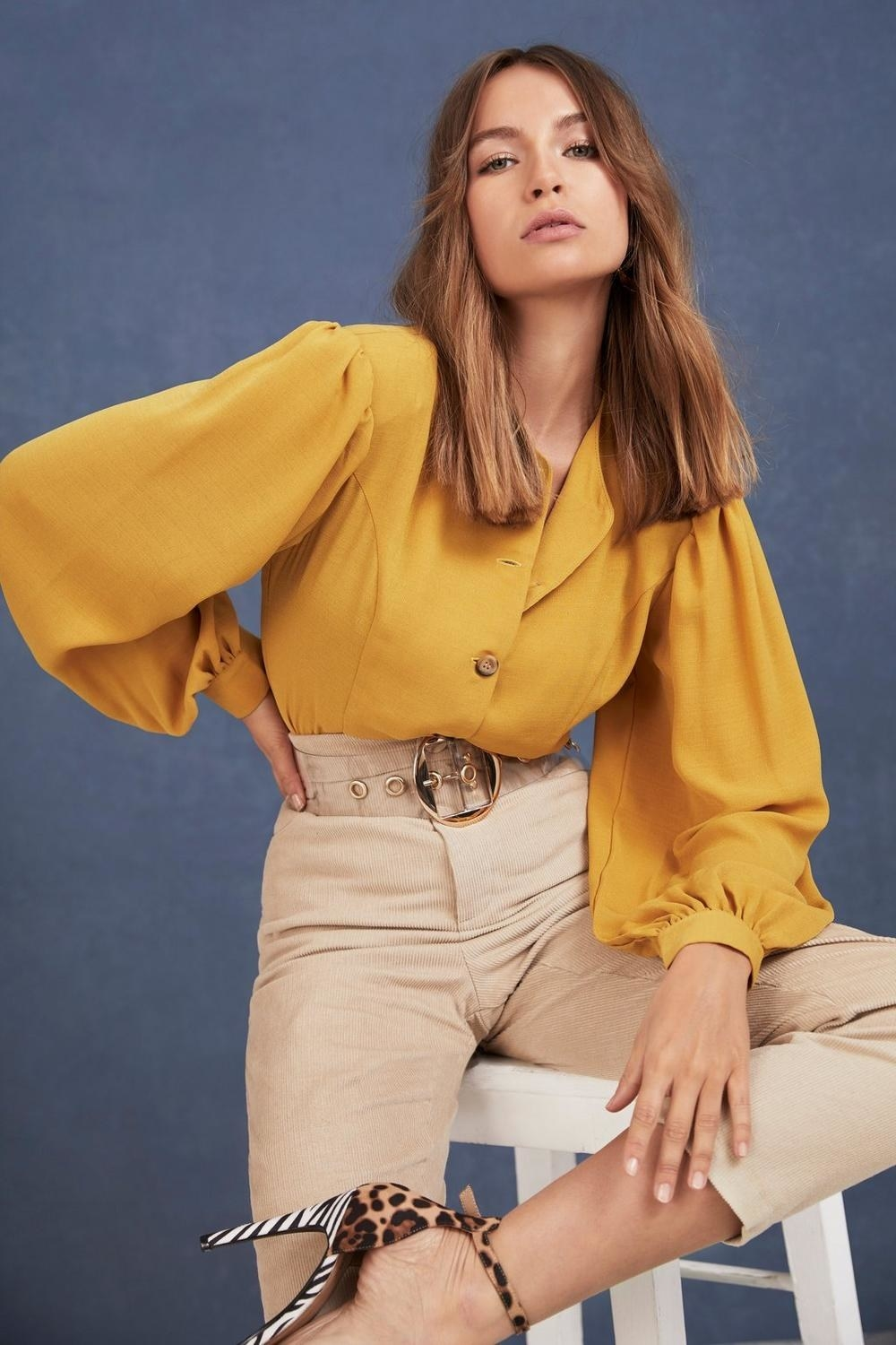 Model wearing the mustard yellow blouse tucked into high-waisted pants