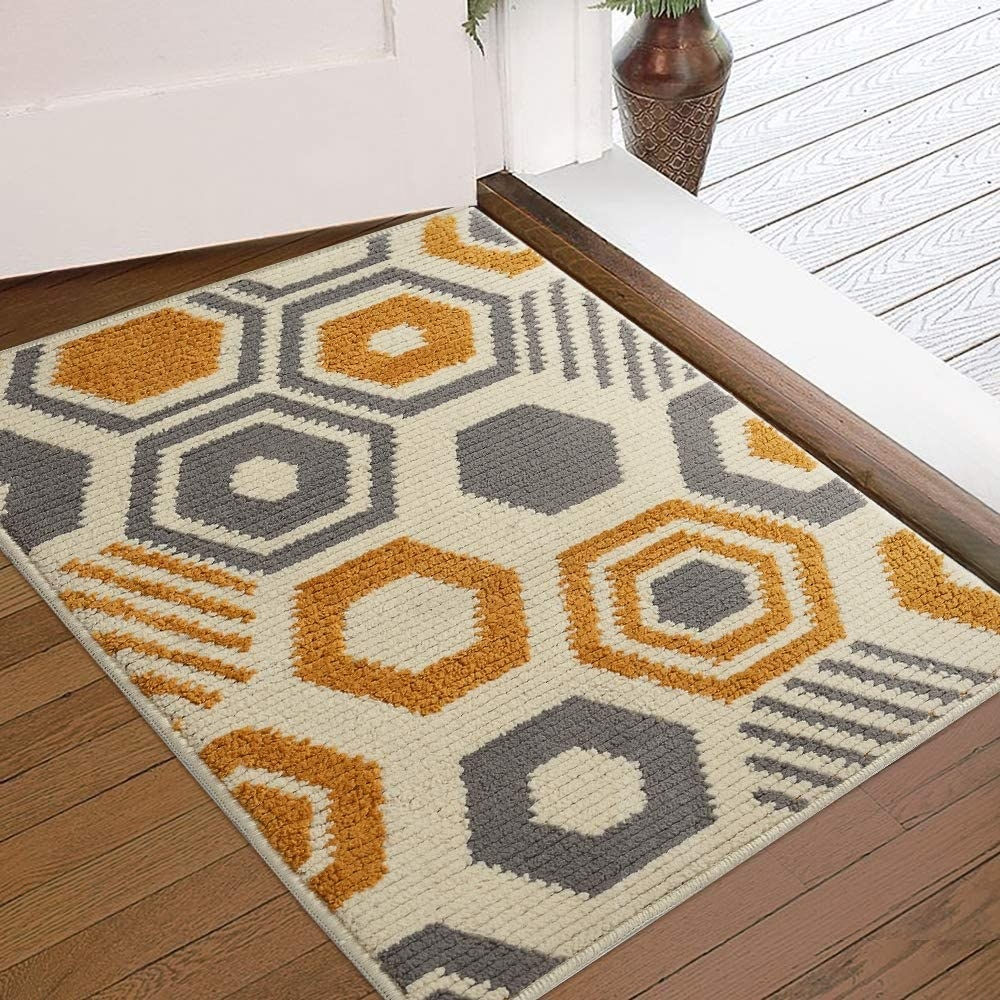 A cream-colored rug with orange and gray geometric shapes