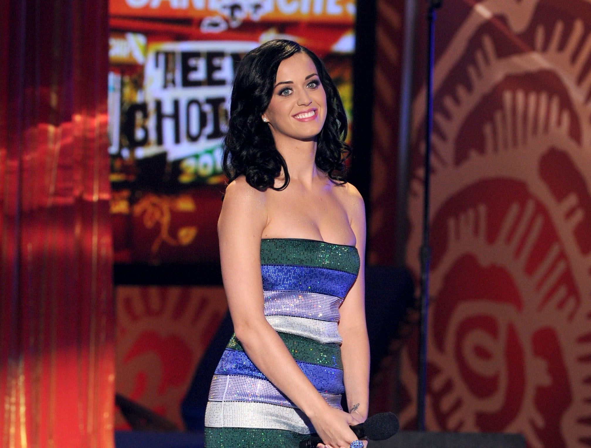Katy Perry standing on stage at the Teen Choice Awards in a green, blue, lavender, and silver tube dress.
