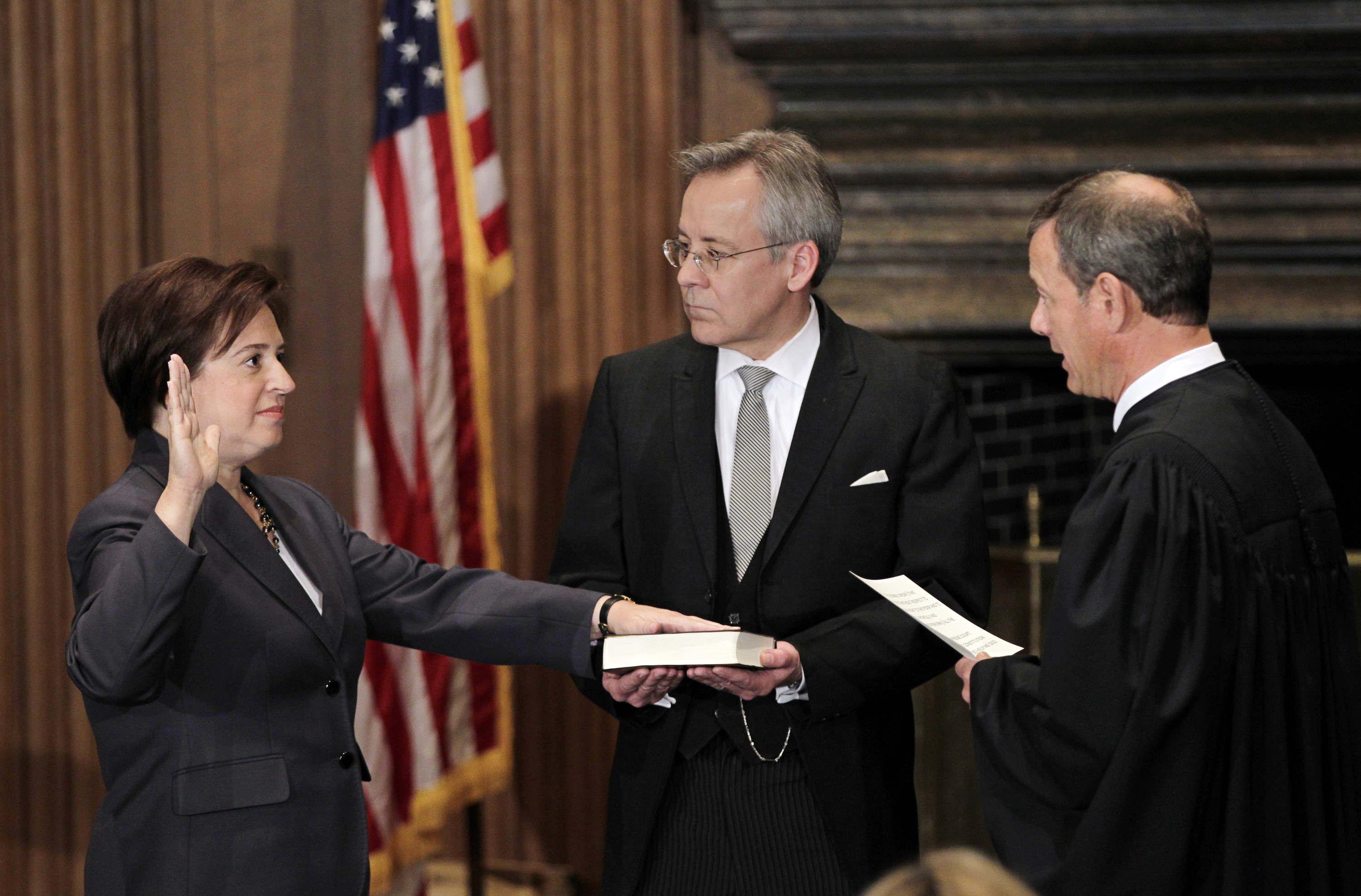 Elena Kagan being sworn in as Chief Justice John Roberts administers the judicial oath, and Jeffrey Minear, counselor to the chief justice, holds the Bible Elena has her hand on.
