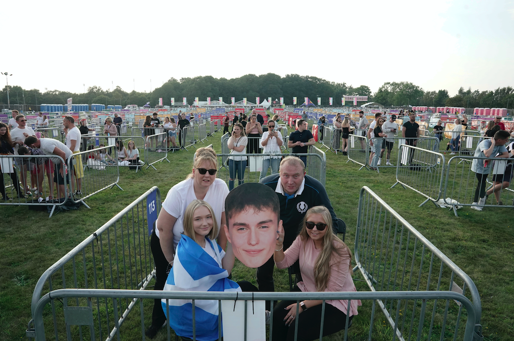 People with a cut-out giant head in a pod