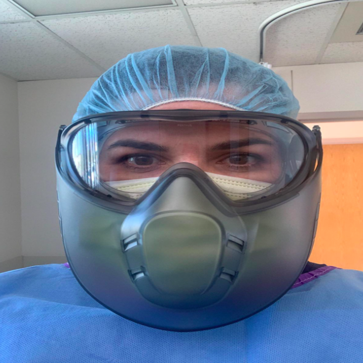 A healthcare professional showing their protective eye wear is fog-free even while wearing a mask and protective face shield