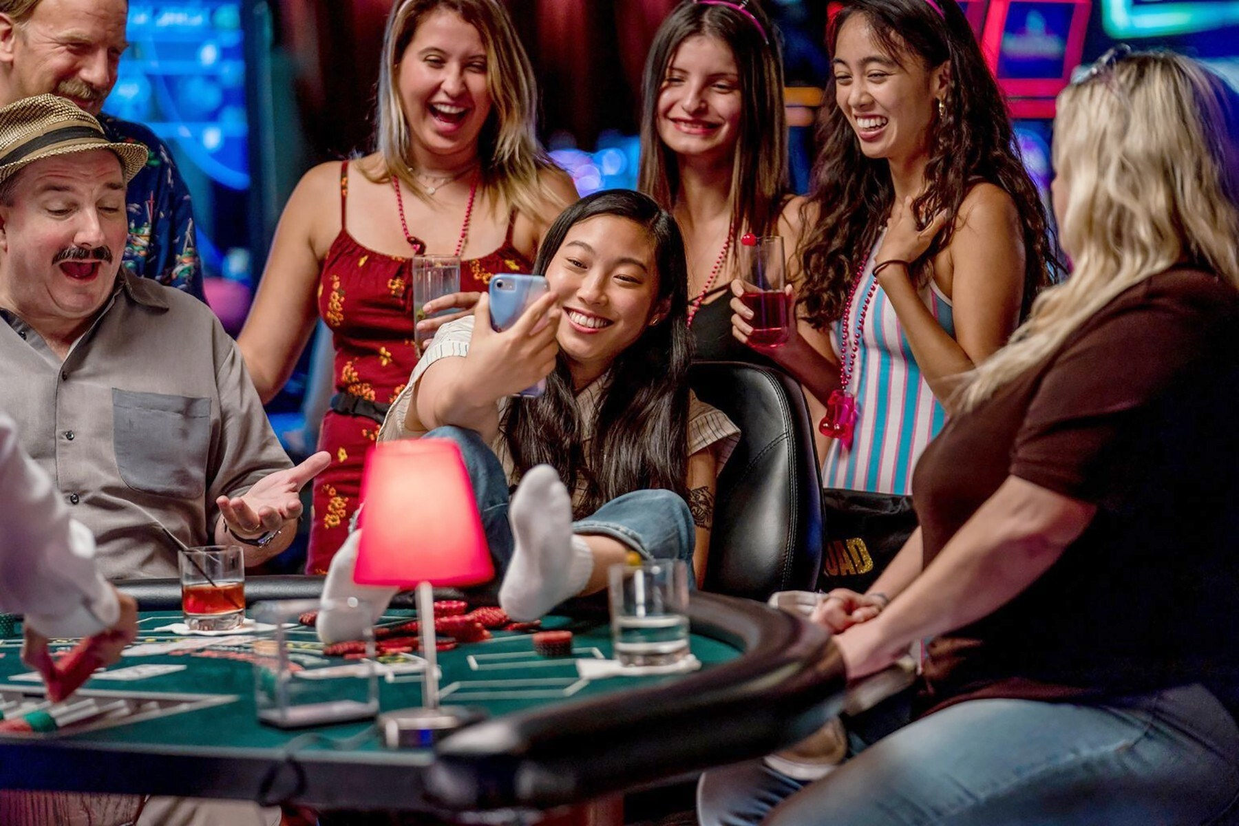 Awkwafine smiling with her feet up on a poker table taking a selfie with three people