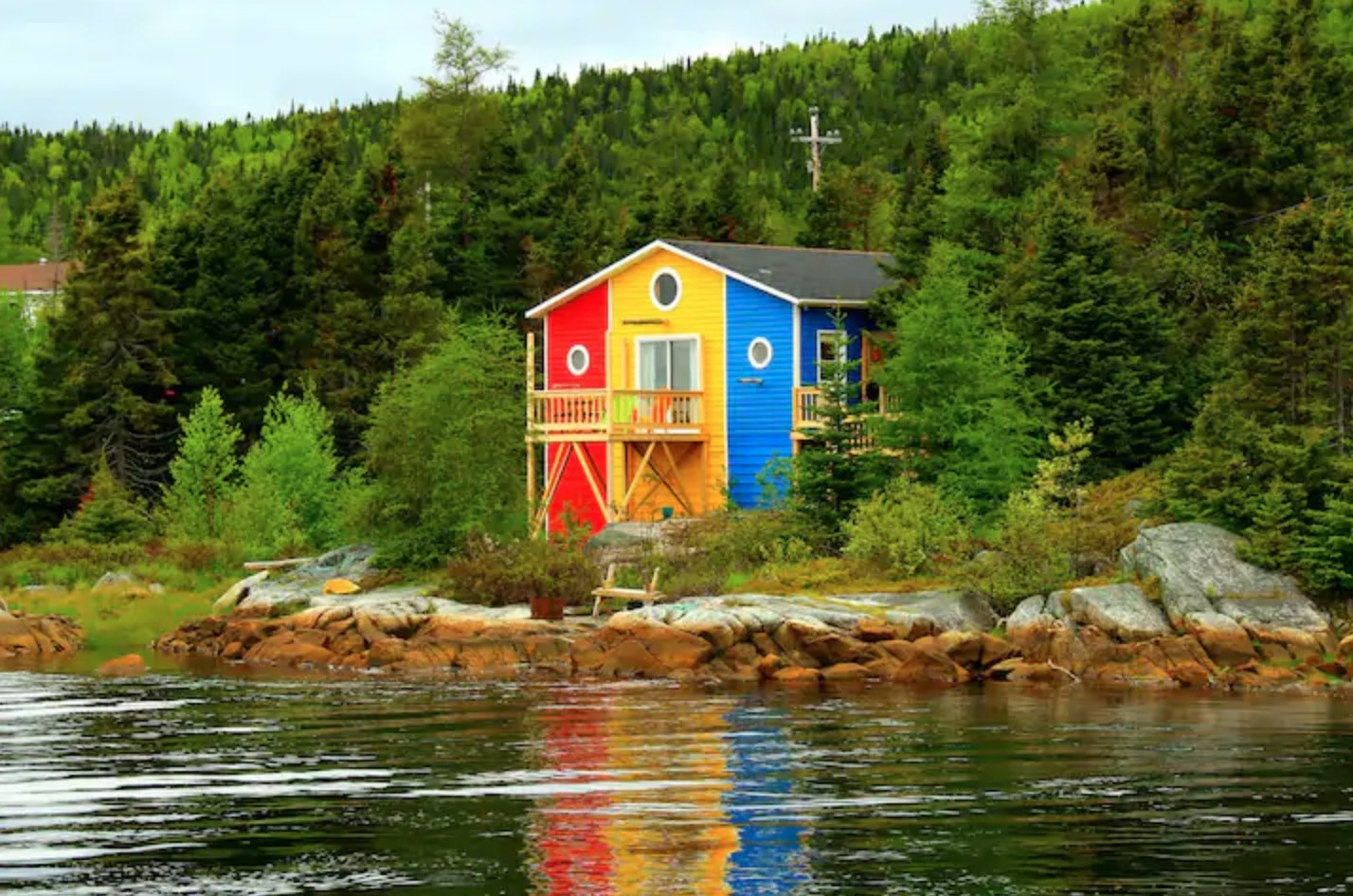 A two-story home painted in red, yellow, and blue stripes with circular windows sits on some rocks near the water in front of a forest.