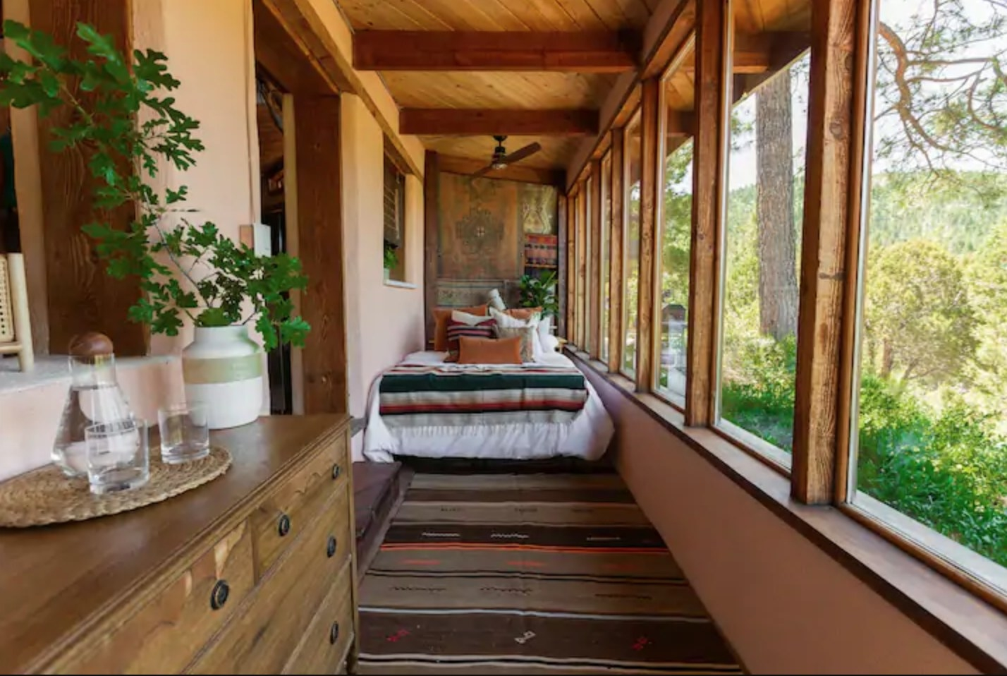 A bed dressed in warm-toned pillows sits nestled in a narrow space between a wall and a large glass window that extends all the way across the room and looks out into the forest.