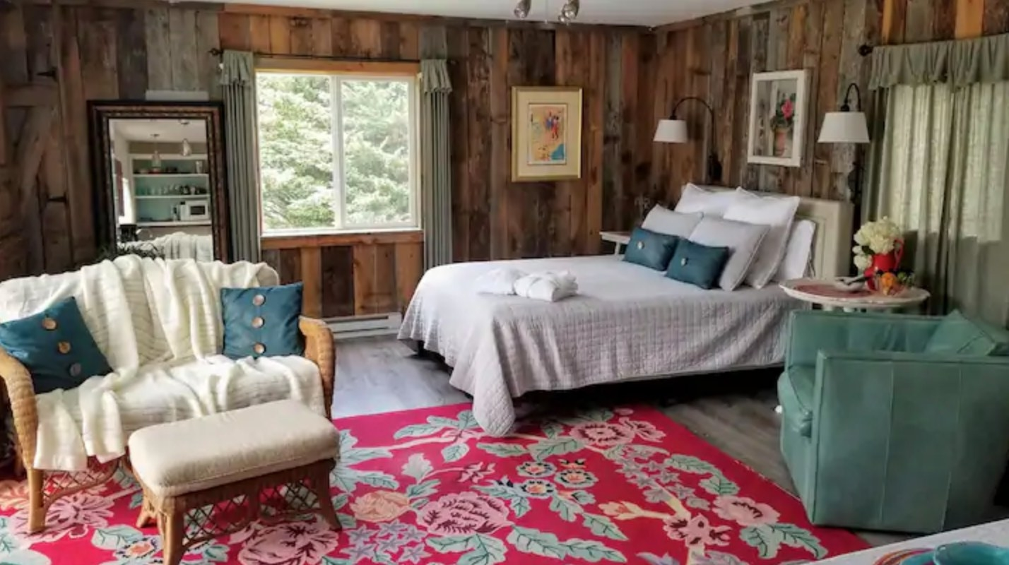 A room with wood-panelled walls and flower-patterned rug is filled with cozy furniture like a wicker love seat draped with a blanket.