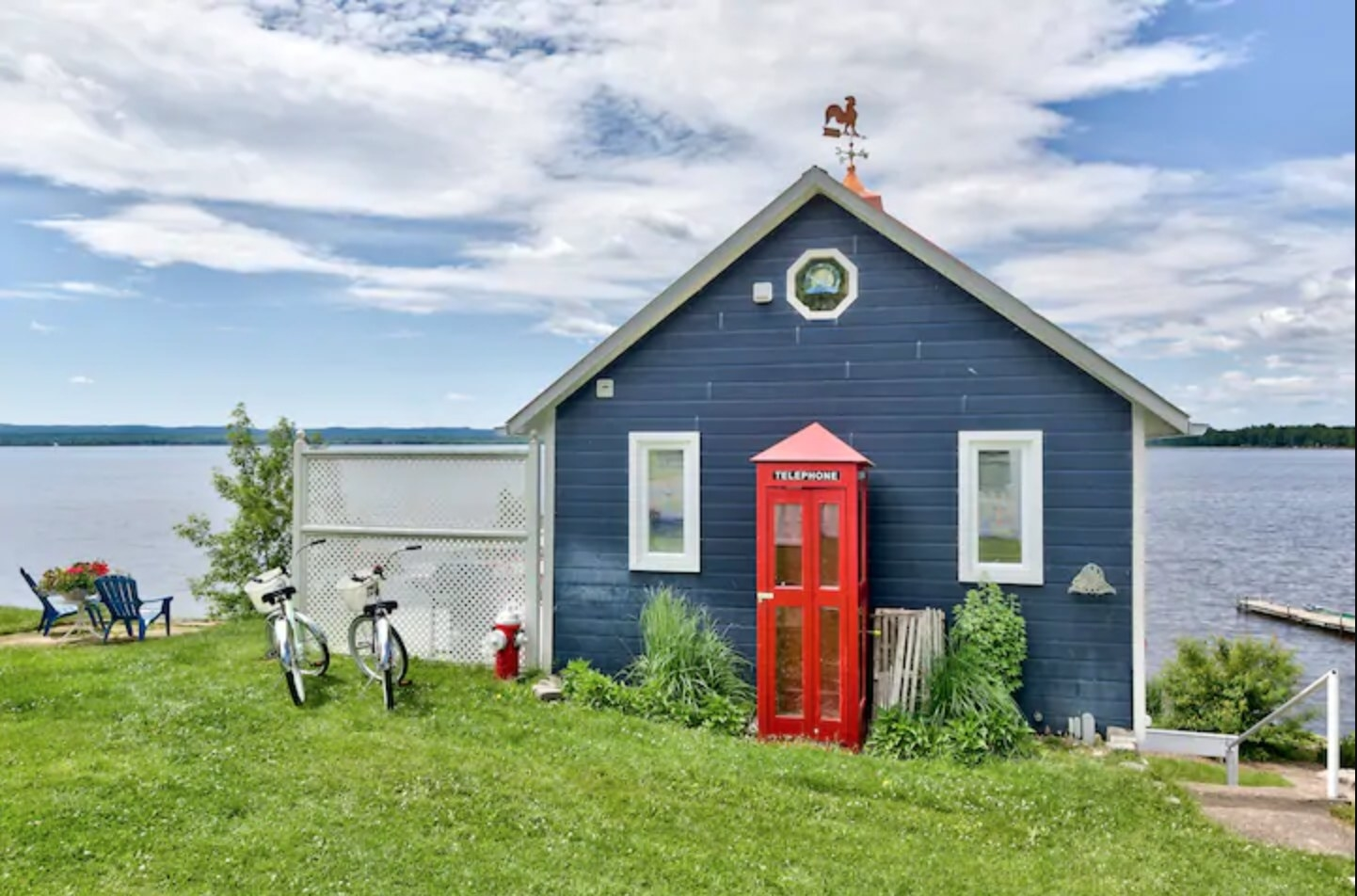 Two bikes sit on the lawn in front of blue house on the lake that is decorated with a red London-style telephone booth.