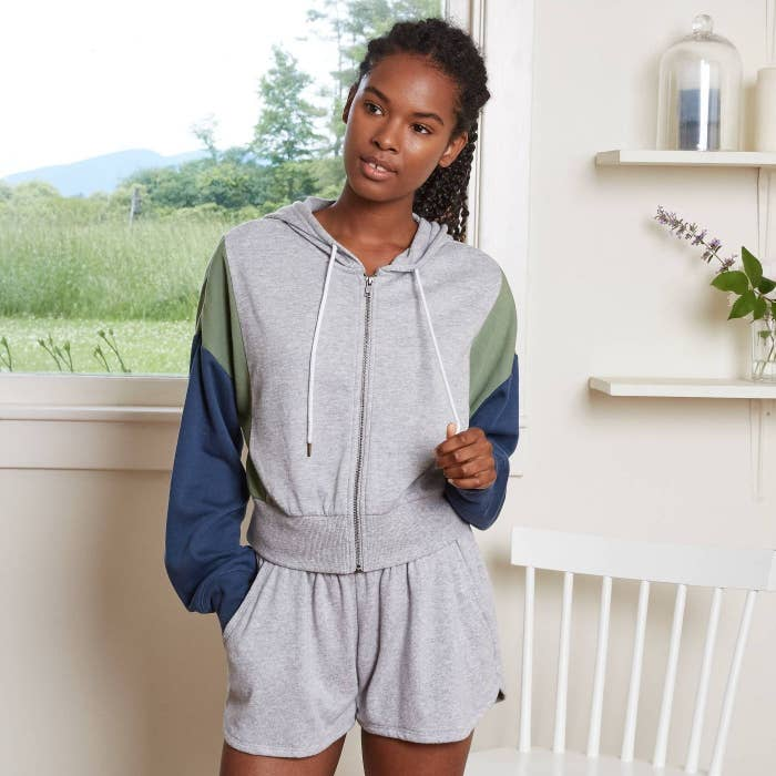 model wearing gray drawstring zip-up hoodie with green and blue sleeves