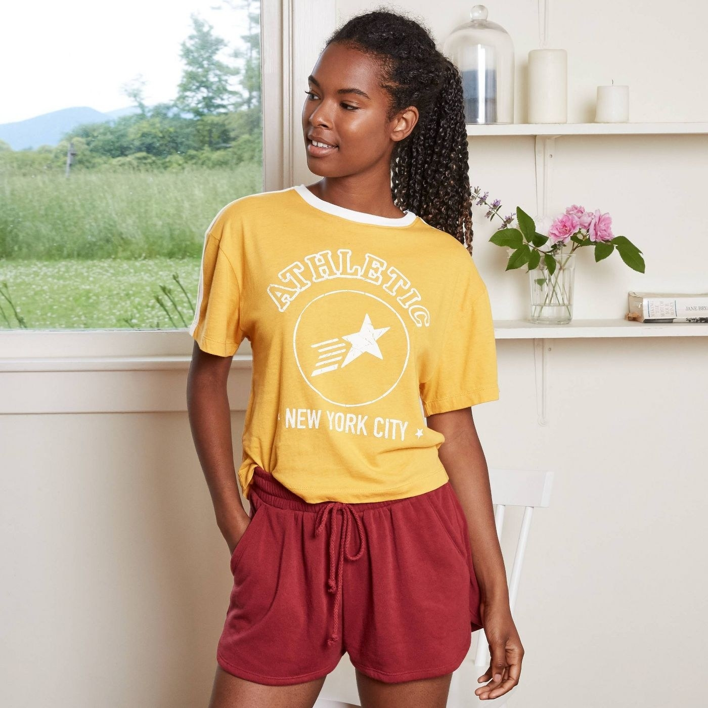 model wearing yellow graphic tee