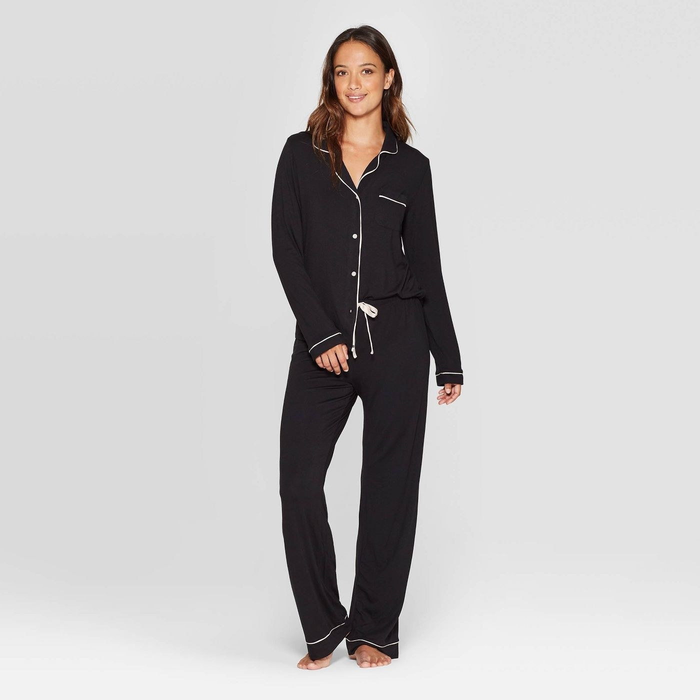 model wearing matching black pants and button-up top pajamas