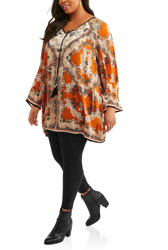 Model wearing an orange and cream tunic with tassels